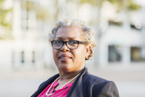 A mature, professional African-American businesswoman standing outdoors. She is in her 50s, well-dressed with short, gray hair and eyeglasses.