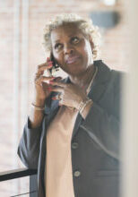 A mature African-American woman in her 50s talking on a mobile phone. She is a businesswoman in an office building.